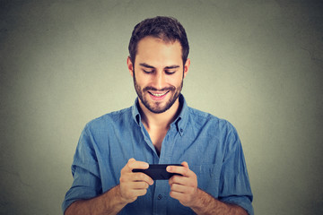 Smiling man looking at his smart phone while text messaging or watching video