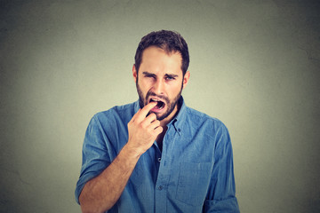 disgusted man with finger in mouth displeased with situation ready to throw up
