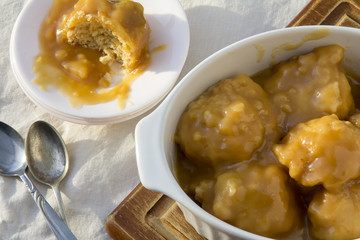 Golden Syrup Dumplings on Table with One portion on Plate with Bite Taken from Above