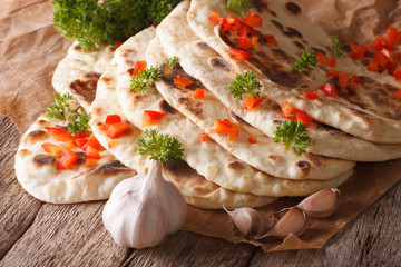 Indian Naan flat bread with garlic and herbs closeup. horizontal