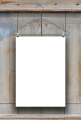 One hanged paper sheet with hanger on stained and weathered wooden board background