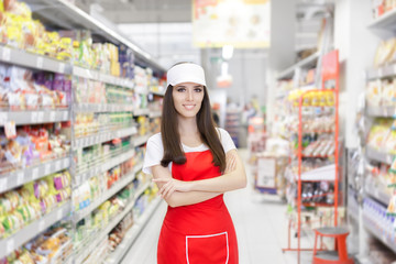 Smiling Supermarket Employee Standing Among Shelves - Portrait of a young sales clerk in a market store
