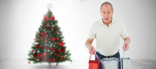 Composite image of shocked man holding shopping bags