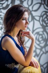 Молодая девушка сидит на диване в синем платье