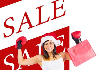 Festive brunette in boxing gloves holding shopping bags