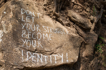 Don´t let your struggle become your identity. Creative motivation concept written on a rock.