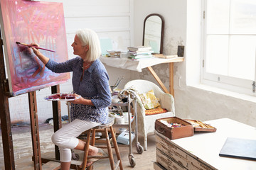 Female Artist Working On Painting In Studio Wall mural