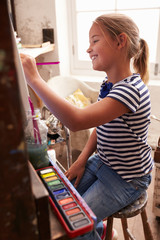 Young Girl Working On Painting In Studio