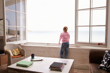 Girl Standing At Window And Looking At Beautiful Beach View