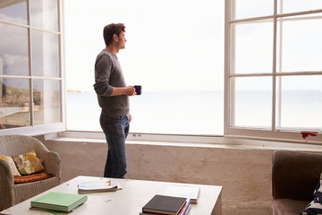 Man Standing At Window And Looking At Beautiful Beach View