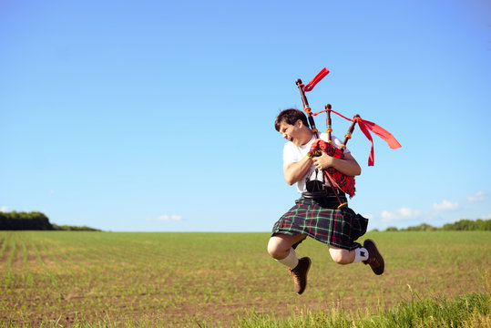 Picture of male jumping high with pipes in Scottish traditional kilt on green outdoors copy space summer field background