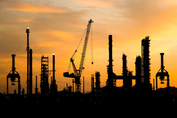 Silhouette of Oil refinery factory during construction at sunset