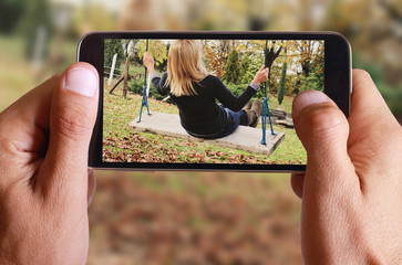Male hand taking photo of Young woman sitting on swing in fall autumn park or garden. Happiness and freedom concept with cell, mobile phone.