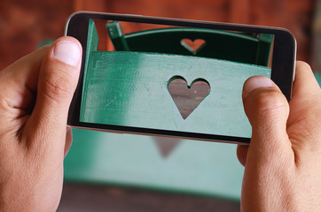 Male hand taking photo of Love concept, two wooden chairs decorated with heart shape. Happy valentine's day background with cell, mobile phone.