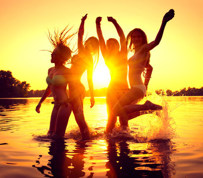 Beach party. Group of happy girls dancing in water on beautiful summer sunset.