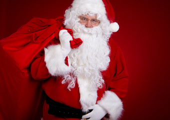 Santa Claus carrying big bag , on red background