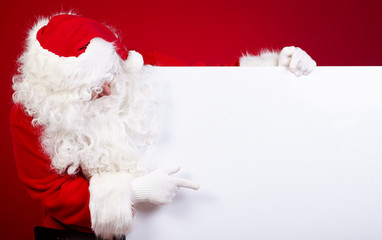 Santa Claus pointing in white blank sign with smile,christmas  r