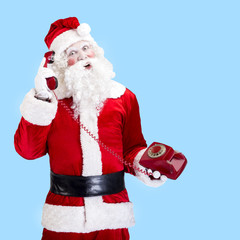 Santa Claus with red telephone posing on blue background