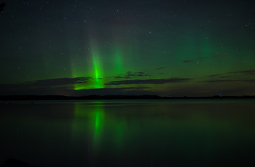 Northern lights over calm lake in Sweden (Aurora borealis)