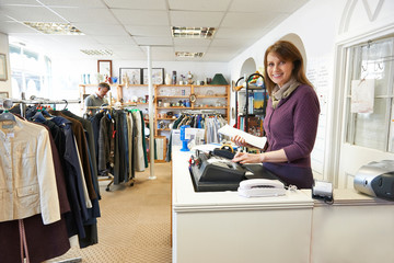 Volunteer In Charity Shop With Customer