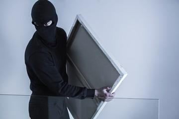 Masked criminal holding stolen picture