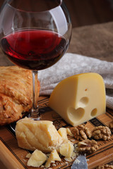 A glass of wine, hard, aged cheese and nuts..