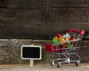 trolley with gift boxes over wooden background