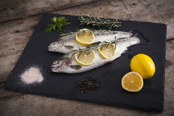 Delicious fresh fish on dark vintage background. Fish with aromatic herbs, spices and vegetables - healthy food