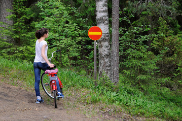 A girl with a bicycle standing on a forest road before a road sign in the sports center, Vierumaki.