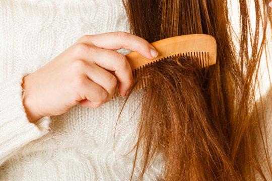 Female hand combing long hair.