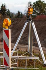 Baustelle zur Landvermessung mit Warnbake und Theodolit, vertikal