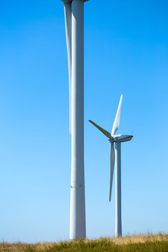 verticale de deux éoliennes sur bleu ciel et sol d'herbe