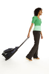 Side view of a smiling woman pulling her rolling luggage.