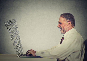 senior man typing on his laptop computer with screen made of alphabet letters