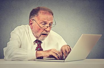 Confused surprised senior man using a pc laptop computer .