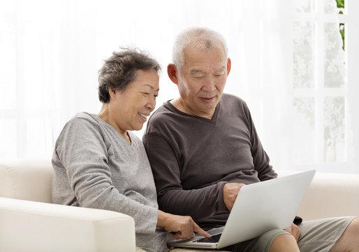 happy Senior Couple Using Laptop on sofa
