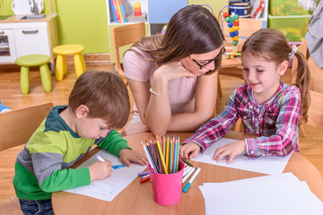 cute girl and boy with kindergarten teacher