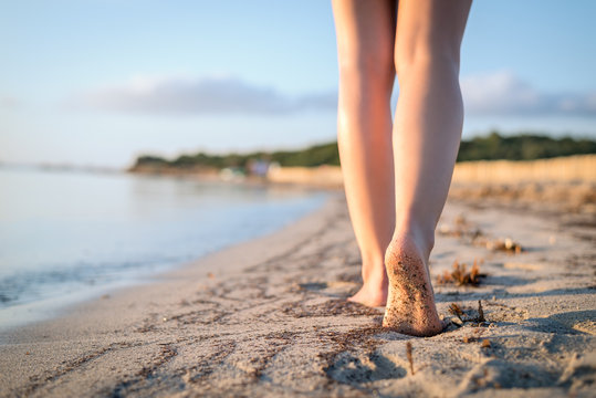 Woman walking on the beach at sunrise enjoying her leisure, Piantarella beach, Corsica France