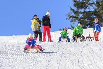 Familie beim Rodeln im Winter