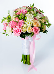 Close-up of bridal bouquet in pink colors on a gray background.