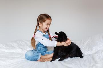 Little girl and black spitz