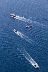 Yacht navigates into beautiful blue water near Santorini island,