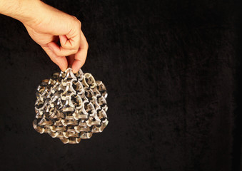 Hand holding artistic composition - cube made of aluminum spacers and zip ties