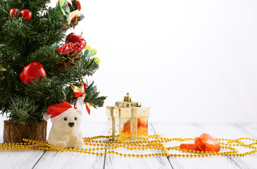 Christmas tree, gold gift box, balls, toy bear, candies and decorations on retro vintage white table isolated on white background