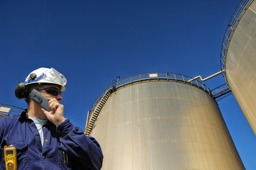 oil worker with large industrial fuel storage tanks inside refinery