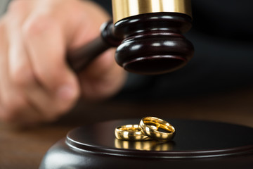 Divorce Judge Hitting Gavel On Golden Rings At Desk
