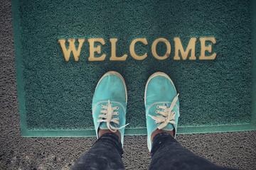 Selfie of sneakers with welcome doormat