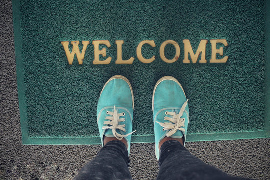 Selfie of sneakers with welcome doormat
