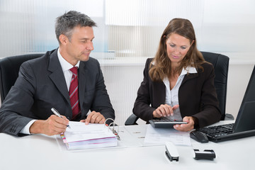 Two Businesspeople Calculating Tax In Office