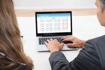 Fototapete - Businesspeople Looking At Calendar On Laptop
